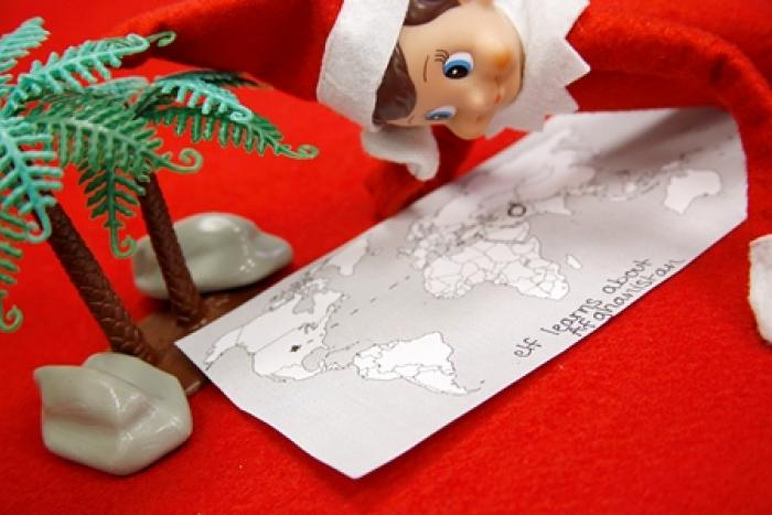 Elf on the Shelf looking at a map