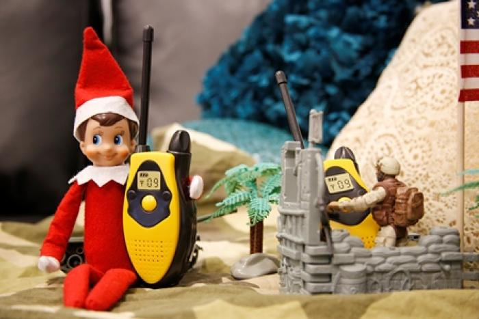 Elf on a Shelf talks to another soldier on walkie talkies