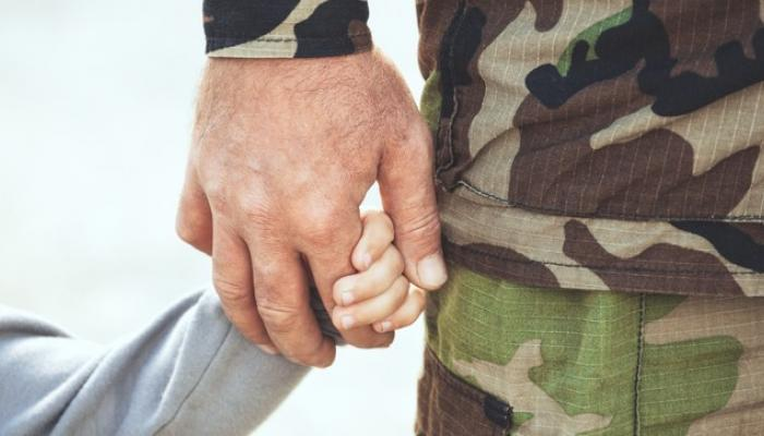 military father holding hand of his child