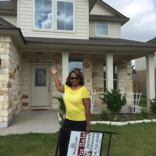 Arthenia T. stands in front of her new home holding the sold sign.